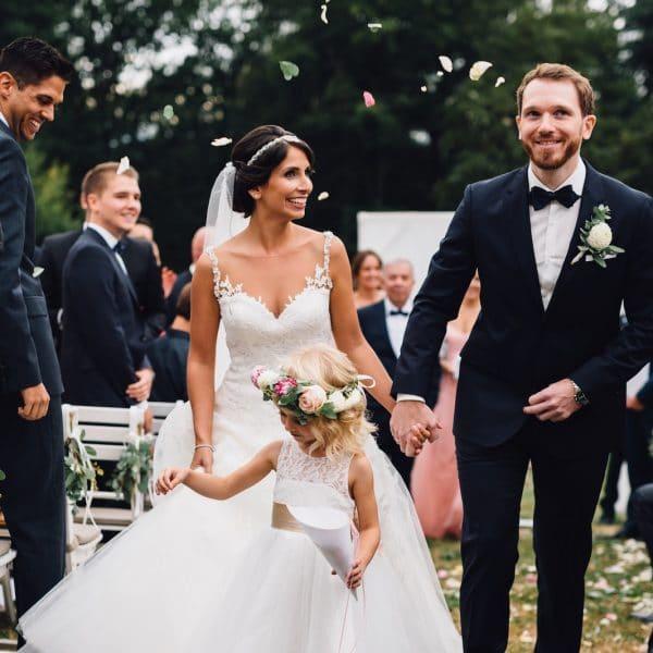 Brautpaar und Blumenkind nach Trauung auf der Wiese