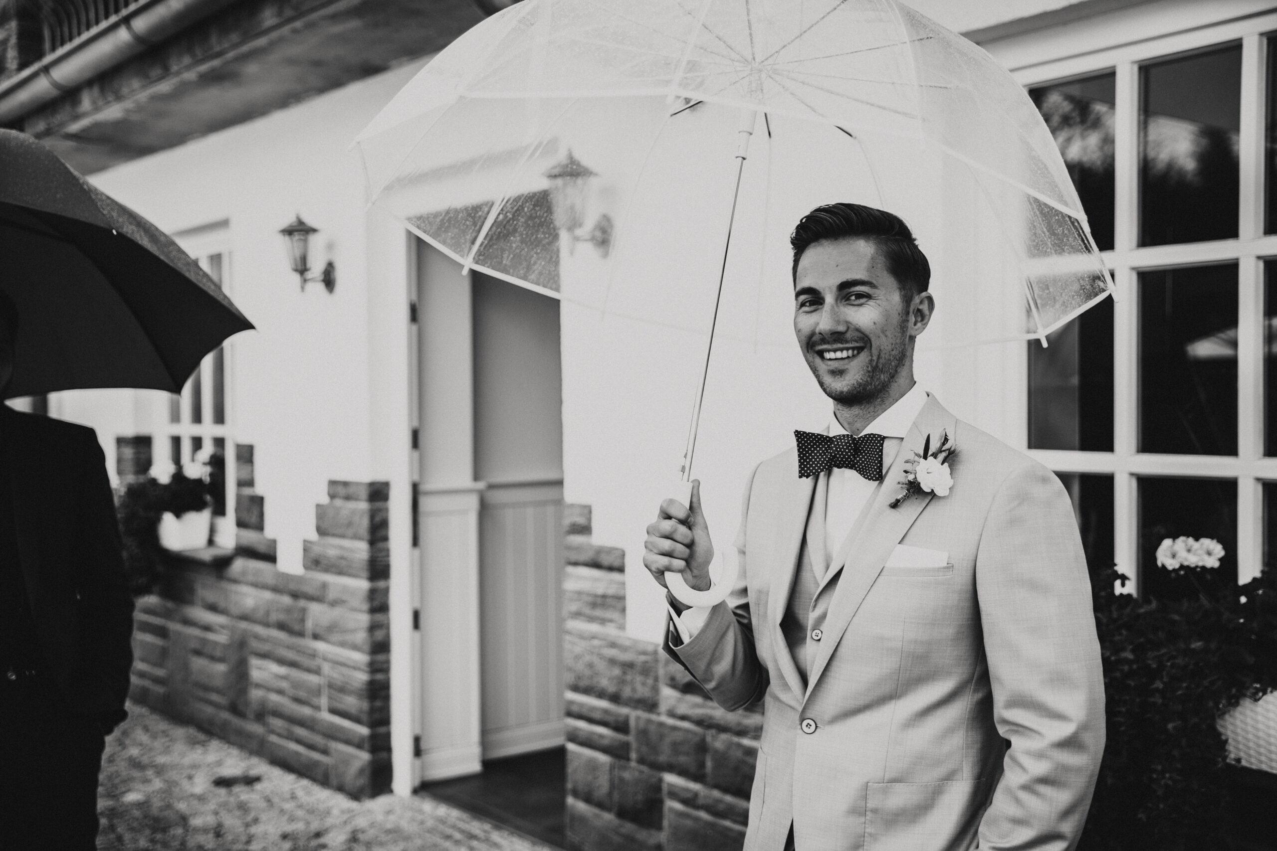 Hochzeitslocation - Hoher Darsberg in der nähe von Heidelberg, Stuttgart in Süddeutschland. Der Bräutigam steht glücklich draußen der Hochzeitslocation und begrüßt seine Gäste. Wahrscheinlich weiß er dass er alles richtig gemacht hat. Da er eine Hochzeitslocation gebucht hat die für schlechtes Wetter ein tollen Plan B hat.