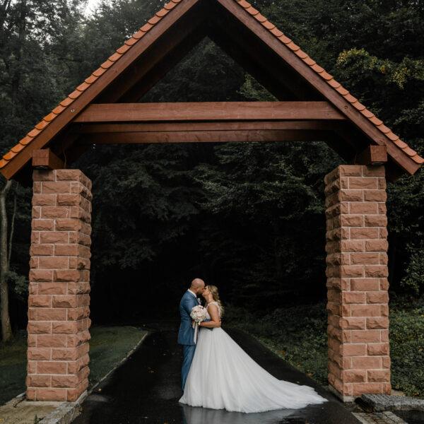 Hochzeit findet an bei schlechten Wetter statt. Das Brautpaar hat sich zum Fotoshootings am Eingang platziert. Der Plan B der Hochzeit ist aufgegangen, alle Gäste feiern eine ausgelassene Traumhochzeit auf der Anlage in Süddeutschland und das Braut posiert entspannt und glücklich vor der Kamera