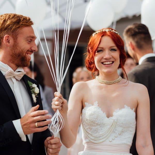 Brautpaar lässt draußen Luftballons steigen