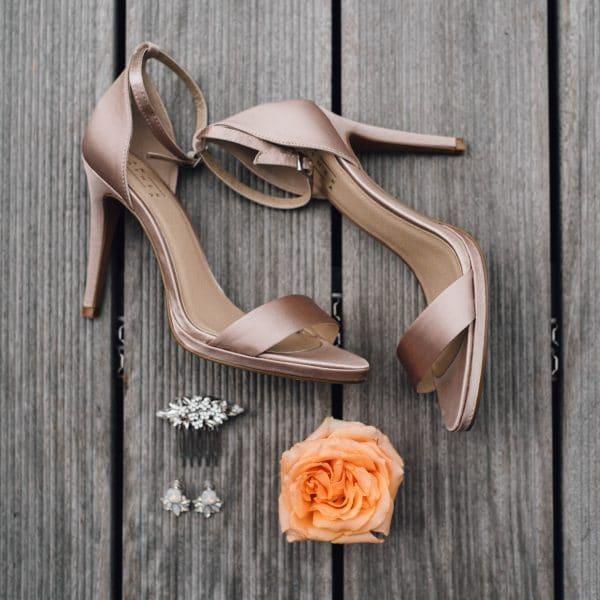 Hochzeitsvorbereitungen: Brautschuhe, Blume und Ohrringe