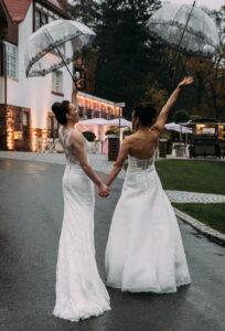 Das Brautpaar jubelt trotz regen - und lässt die Regenschirme fliegen. Wahrscheinlich weil die Hochzeitslocation eine tollen Plan B beim Regenwetter hat.