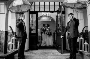 Hochzeitslocation Hoher Darsberg - Süddeutschland - Traumhochzeit - Es regnet - Gleichgeschlechtliches Brautpaar - werden von den Trauzeugen mit Regenschirmen erwartet - sie küssen sich am Eingang bevor sie nun zum Traualtar schreiten. Trotz schlechtem Wetter ist das Brautpaar super glücklich- eine wunderschöne Hochzeit im Frühjahr.